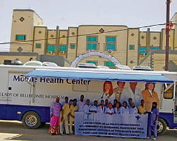 Group of people holding a banner in front of a mobile health center.