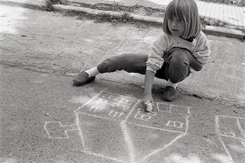 Little girl drawing on a sidewalk with chalk.