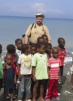 Dr. Tim Bristol surrounded by a group of young children in Haiti.