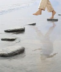 Photograph of feet using stepping stones to navigate the beach.