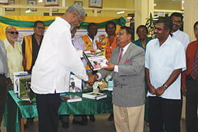 Dr. Shamir Andrew Ally presents books to the University of Guyana library.