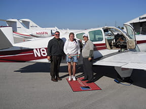 Three people standing in front of a plane.